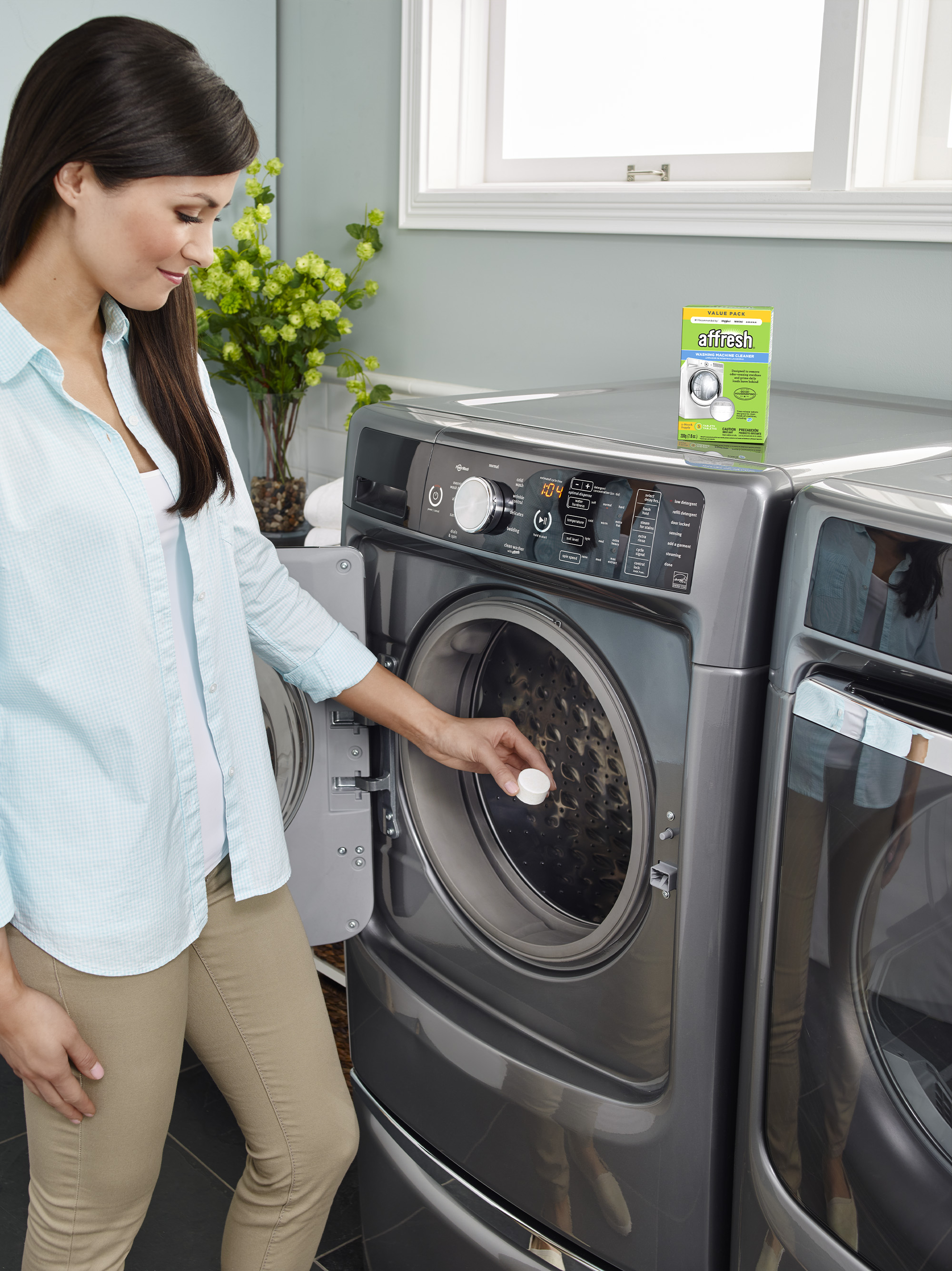 A long-haired woman in an aqua shirt places an affresh Washing Machine Cleaner tablet into the drum of her front-load washer and prepares to run the